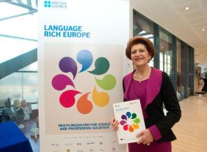 "Androulla Vassiliou posing in front of the poster of the ""Language Rich Europe"" networking project"